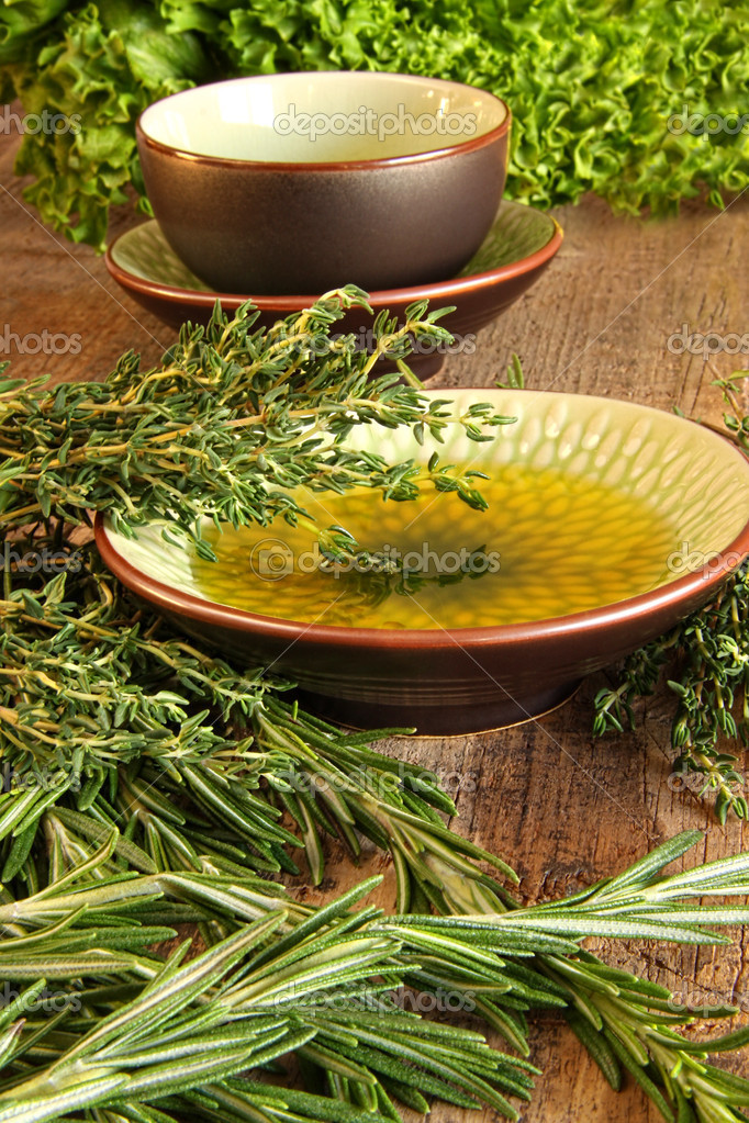 Fresh herbs with olive oil on wooden cutting board — Stock Photo #8557336