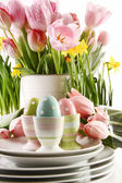 Easter eggs in cups with spring flowers on white — Stok fotoğraf