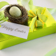 Gift, card and egg in nest for Easter - Stock Photo