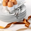Brown eggs with plates for Easter breakfast - Stock Photo