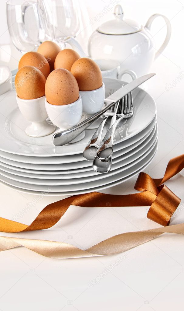 Brown eggs with plates for Easter breakfast on white — Stock Photo #9164455