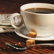 Coffee cup and newspaper. Focus on handle of cup — Stock Photo