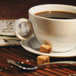 Coffee cup and newspaper. Focus on handle of cup - Stock Photo