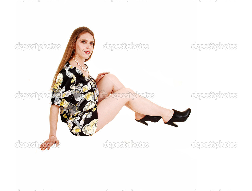 A woman in a dress and high heels sitting on the floor in the studio with long blond hair, showing her nice legs, isolated on white. — Stock Photo #9645350