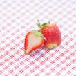 Strawberries lying on plaid fabric — Stock Photo