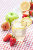 Cocktail with ice,lemon,apple, fig and strawberries on a plate — Stock Photo