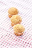 Tre muffins på rutigt tyg — Stockfoto