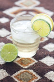 Water with lemon and lime in a glass with ice on ethnic mat — Stock Photo