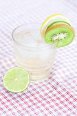 Water with lemon and lime,kiwi in a glass with ice — Stock Photo