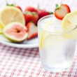 Cocktail with ice,lemon, fig and strawberries on a plate — Stock Photo