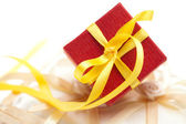 Red gift box with a yellow ribbon on a cushion for the rings — Stock Photo