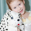 Portrait of a beautiful little girl with a toy dog — Stock Photo