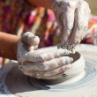 Hand on a potter wheel at the fair — Stock Photo