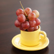 Stock Photo: Grapes in cup and saucer on wooden table