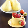 Strawberries, pears on a plate and cup with saucer on a wooden t — Stock Photo