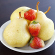 Strawberries and  pears on a plate on a wooden table — Stock Photo