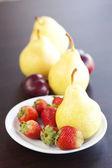 Fresa en placa, uvas y peras en una mesa de madera — Foto de Stock