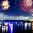 Fireworks firing up into the sky with a boat on a river below them, with a — Stock Photo