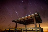 Track star long exposure and the wooden pavilion — Stock fotografie