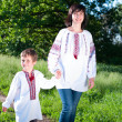 Stock Photo: Mother and son in traditional ukrainian shirt walk on the meadow