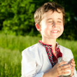 Little ukrainian boy drinks milk outdoors — Stock Photo #10664342