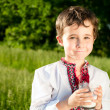 Little ukrainian boy drinks milk outdoors — Stock Photo #10664357