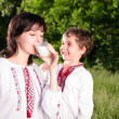 Mother and son in traditional ukrainian shirt drink milk outdoor — Stock Photo #10664361