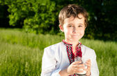Little ukrainian boy drinks milk outdoors — Stock Photo