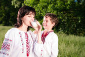 Mother and son in traditional ukrainian shirt drink milk outdoor — Stock Photo