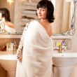 Smiling womin bathroom by mirror wrapped in mantle — Stock Photo #8056265