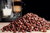 Coffee beans heap and coffee machine — Stock Photo