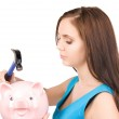 Teenage girl with piggy bank and hammer — Stock Photo #7969801