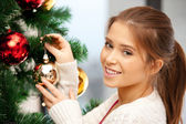 Woman decorating christmas tree — Stockfoto