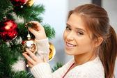 žena zdobení vánoční strom — Stock fotografie