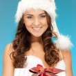 Santa helper girl with gift box — Stock Photo