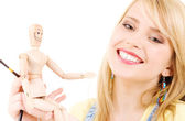 Happy teenage girl with wooden model dummy — Стоковое фото
