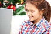Happy woman with laptop and christmas tree — Stock Photo