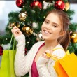 Happy woman with shopping bags and christmas tree — Stock Photo #8021915