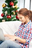 Mujer feliz con portátil y árbol de navidad — Foto de Stock