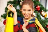 Gelukkige vrouw met shopping tassen en kerstboom — Stockfoto