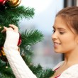 Woman decorating christmas tree - ストック写真