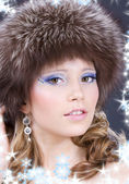Lovely woman in furry hat over grey — Stock Photo