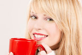 Happy teenage girl with red mug — Stock Photo