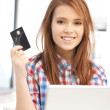 Happy woman with laptop computer and credit card — Stock Photo #8701494