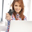 Happy woman with laptop computer and credit card — Stock Photo #8730625