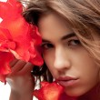 Lovely woman with red flowers — Stock Photo