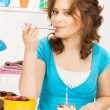 Lovely housewife with cake and candle - Stock Photo