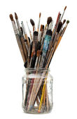 Assorted dirty painting brushes in glass flask — Stock Photo