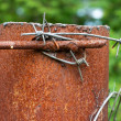 Rusty column with barbed wire — Stock Photo