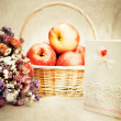 Stock Photo: Apples in basket and wild flowers